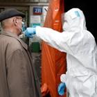 Медицински служител мери температурата на човек на входа на болница във Варшава.