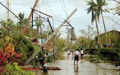 Местни жители заобикалят унищожен след тайфун електрически стълб в централната част на Филипините през 2016 г.
