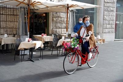 Жена с колело минава покрай празен ресторант в Рим.