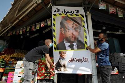 Продавачи в арабския квартал на Йерусалим поставят плакат срещу Макрон.