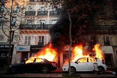 Протестите завършиха с палежи на коли в центъра на Париж, след като в мирното шествие се включиха млади момчета с качулки. СНИМКА: РОЙТЕРС
