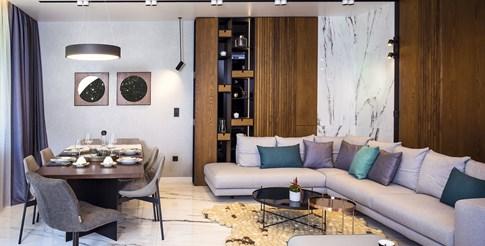 """Обединената всекидневна – мраморът от пода пропълзява и по стените. Кътът с големия ъглов диван, на пода  ръчно изработен килим от плъст, аксесоари от """"Елегант ливинг"""""""