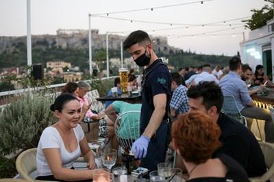 Сервитьор с маска и ръкавици обслужва клиенти на заведение в Атина.