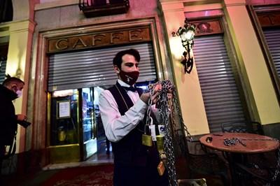 Келнер затваря кафене в Торино след въвеждането на нови ограничителни мерки в Италия. СНИМКА: РОЙТЕРС