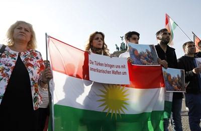 """Хора държат кюрдското знаме при демонстрация срещу Турция. На плака пише на немски """"Турция ни убива с американски оръжия"""". Снимка: Ройтерс"""