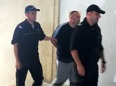 Полицаи водят арестувания шофьор към съдебната зала. Снимка ЕЛЕНА ФОТЕВА