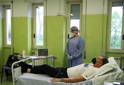 Медик проверява болен от коронавирус в Италия.  СНИМКА: РОЙТЕРС