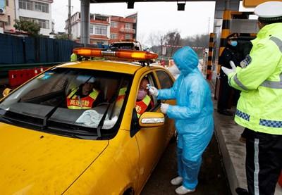Медицински работници мерят температурата на шофьор на контролен пункт н Китай. СНИМКА: РОЙТЕРС