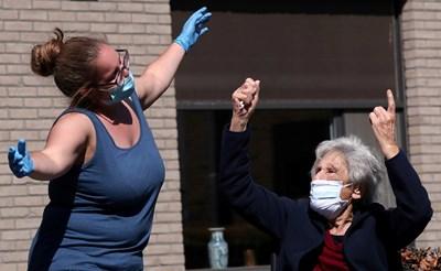Медицинска сестра пее, за да даде кураж на възрастни хора от старчески дом в Белгия по време на епидемията. СНИМКА: РОЙТЕРС