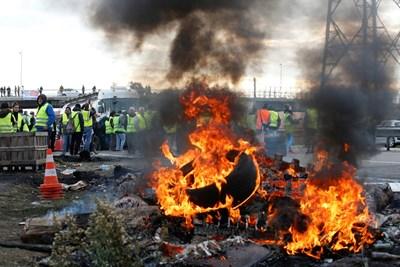 Демонстранти с жълти  жилетки - символ на протеста на шофьорите, палят гуми и блокират достъпа до склад с горива във  Фо сюр мер, Франция.  СНИМКА: РОЙТЕРС
