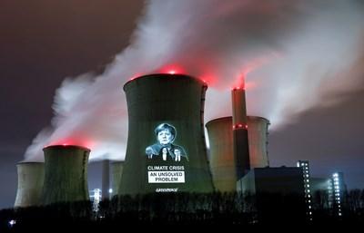 """Активисти на """"Грийнпийс"""" прожектираха образите на канцлерката Ангела Меркел и нейни министри върху ТЕЦ в Нойрат, Германия, с надпис """"Кризата с климата - нерешен проблем"""". СНИМКА: РОЙТЕРС"""