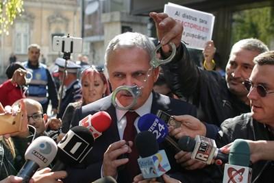 Румънец размахва белезници пред Ливиу Драгня на протест в Букурещ през 2017 г.  СНИМКА: РОЙТЕРС