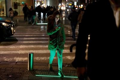 В Тел Авив светещи ленти сигнализират на телефонните зомбита кога да преминат по пешеходна пътека. СНИМКА: РОЙТЕРС