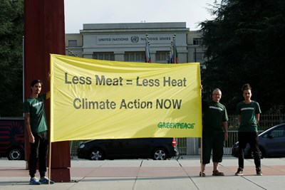 """Екоактивисти от """"Грийнпийс"""" зоват за действия срещу климатичните промени пред централата на ООН в Женева с плакат """"По-малко месо, по-малко жега"""". СНИМКА: РОЙТЕРС"""