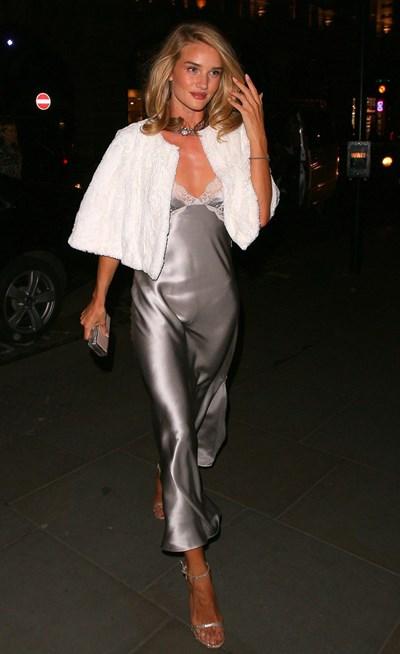 На снимката е моделът Роузи Хънтингтън-Уайтли, която е облечена със сребриста слип рокля. За да направи визията си уместна за вечерта, я комбинира с бяла кожена перелина.