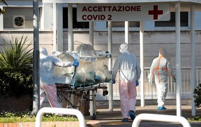 Лекари в защитни костюми докарват пациент с КОВИД-19 на специална носилка в болница в Рим.