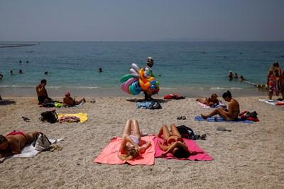 Туристи се пекат на плаж край Атина въпреки горещата вълна..