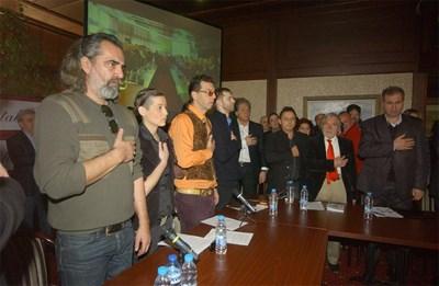 """Участници в дискусията за протестите в столичния ресторант """"Континентал плаза"""" почетоха с едноминутно мълчание паметта на Апостола на свободата Васил Левски. Първият отляво е актьорът Андрей Слабаков, с оранжевата риза - флейтистът Кристиян Коев, с червената вратовръзка е Йоло Денев. СНИМКА: Гергана Вутова"""