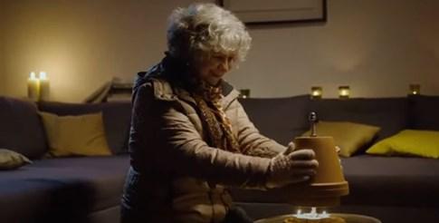 Германска топли ръцете си на загрята от свещи саксия.