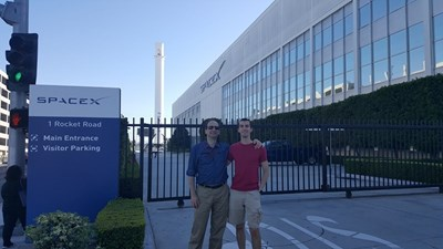 """Орлин Велев-джуниър (вдясно) с баща си пред компанията """"Спейс Екс"""". Отзад се вижда първата ракета, която се върна след изстрелването в Космоса."""
