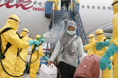 Медицински служители пръскат индонезийски граждани с антисептик след пристигането им от Ухан на летището в град Батам.