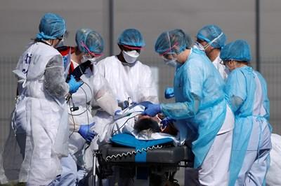 Френски екип пренася пациент от болница в град Мюлуз, преди да бъде качен в хеликоптер. СНИМКА: РОЙТЕРС