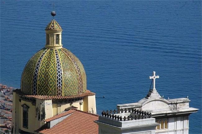 """Църквата """"Санта Мария Асунта"""" с красивия си купол, покрит със сини, зелени и жълти плочки."""