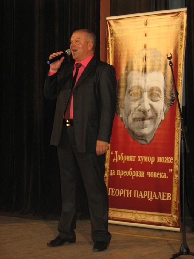 """Венци Мартинов води спектакъла, посветен на Парцалев, на заден план се вижда една мисъл на великия артист - """"Добрият хумор може да преобрази човека""""."""