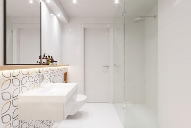 Банята е решена в бяло и изглежда просторна