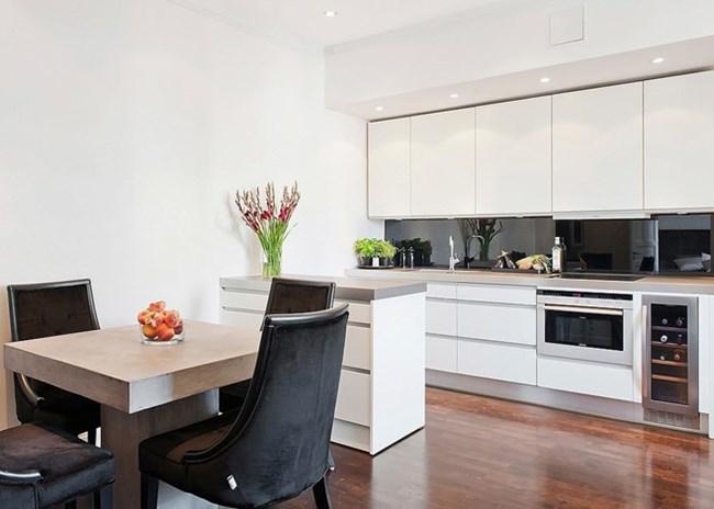 Кухнята е бяла и визуално се слива със стените