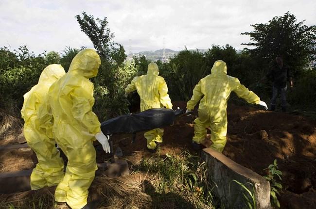 Мъже в защитни облекла погребват умрял от ебола в Гвинея. В началото на епидемията през 2014 г. местните се събират на многолюдни погребения, което умножава броя на заразените.
