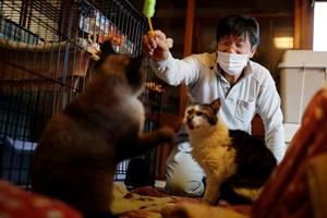 57-годишният мъж играе със спасените от него котки Чарм и Мокун.