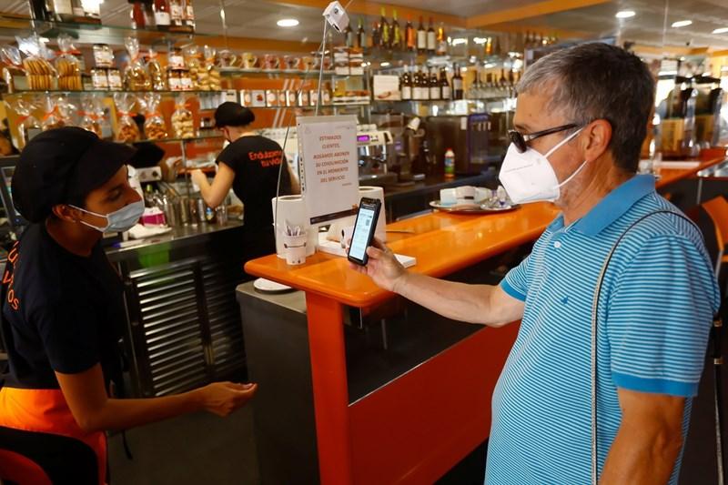 Испанец показва дигитален ваксинационен документ в барче на Канарските острови.