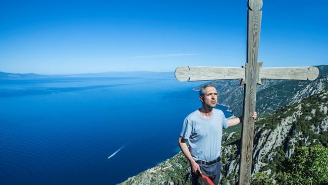 Фотографът Йордан  Симеонов на скала по пътя към връх Атон до поклонническия кръст