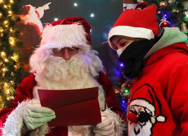 Дядо Коледа чете писмо на малко момченце с подаръците, които е поискало за празника.