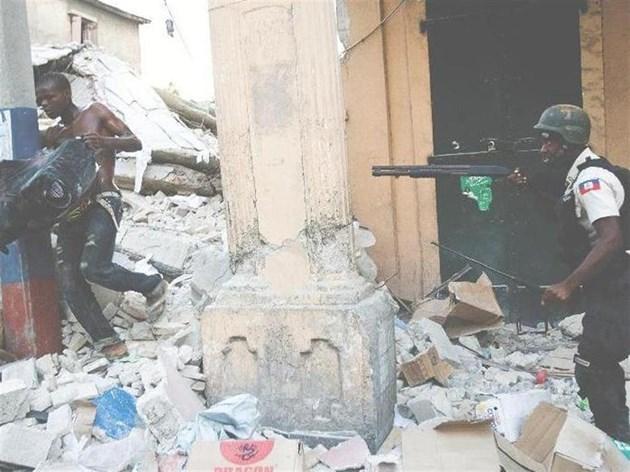 Полицай преследва мародер, който изнася стока от магазин в столицата след труса на 12 януари. Войници на ООН пуснаха сълзотворен газ срещу изгладнелите хаитяни.