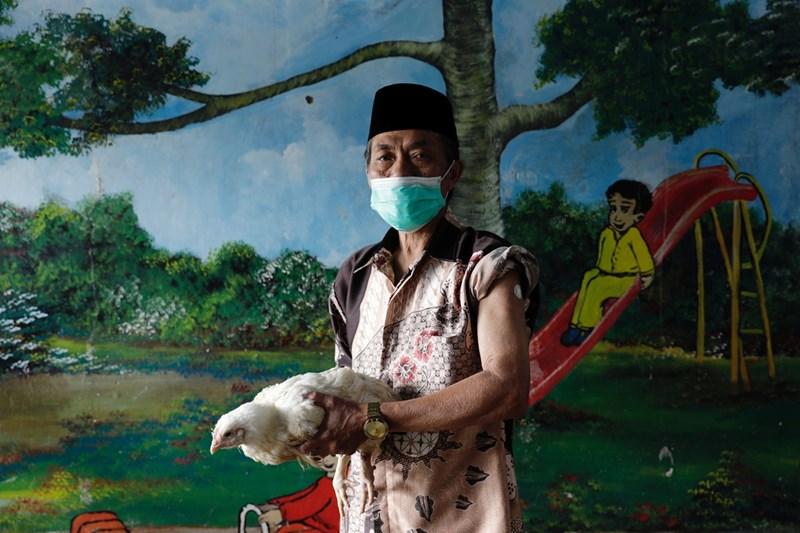 Този ваксиниран човек от Тайланд е получил за награда пиле Снимки: Ройтерс